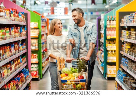 Enjoying shopping together. Happy young couple bonding to each other and smiling while walking while walking in food store with shopping cart - stock photo