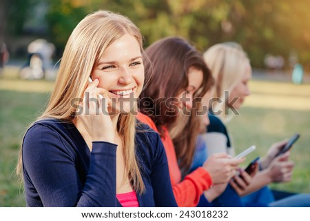 Enjoying student life. Beautiful young woman talking on the mobile phone and smiling while sitting on the grass against university building with her friends using gadgets in the background - stock photo