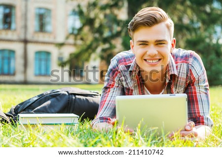 Enjoying student life. Handsome young man working on digital tablet and smiling while lying on grass  - stock photo