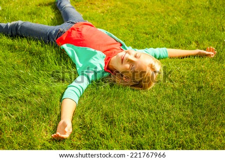 Enjoying summer. Top view of cute little girl lying on the green grass and smiling - stock photo
