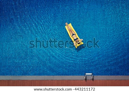 Enjoying suntan. Vacation concept. Top view of slim young woman in bikini on the yellow air mattress in the big swimming pool. - stock photo