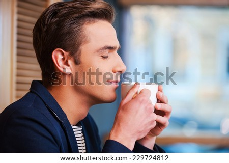 Enjoying the best coffee in town. Side view of handsome young man keeping eyes closed and smiling while smelling cup of fresh coffee in cafe - stock photo
