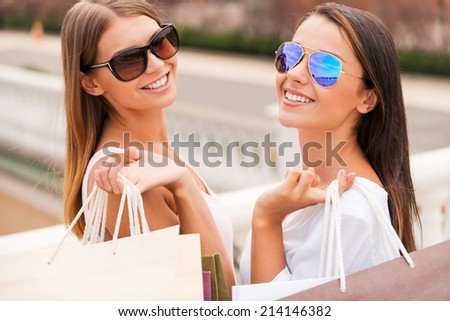 Enjoying the day shopping. Rear view of two beautiful young women holding shopping bags and looking over shoulder with smile while standing outdoors - stock photo