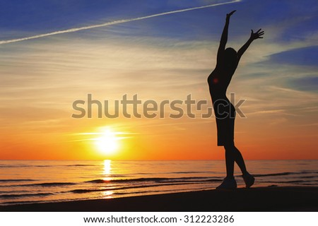 Enjoying the summer sunset. Cheerful slender woman silhouette contemplating the sunset with raised up hands on blue sky background on the beach. Summertime multicolored outdoors horizontal image. - stock photo