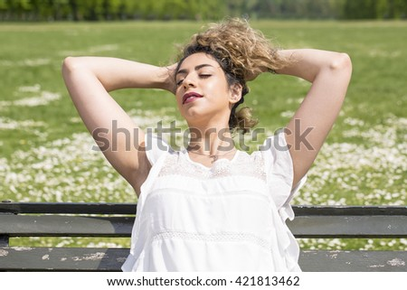 Enjoying the Sunshine. A woman is sensually enjoying the feeling of sunlight on her face after a long winter. She has pulled her hair off her neck with her hands and is leaning back into the bench.