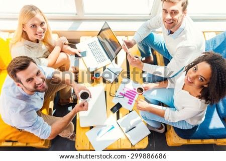 Enjoying their creative occupation. Top view of fourcheerful young people working together while sitting at the wooden desk together - stock photo