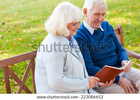Enjoying their favorite book together. Cheerful senior couple reading a book together while sitting on the park bench  - stock photo
