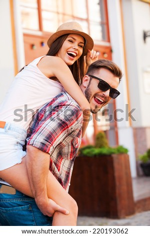 Enjoying their free time together. Happy young man carrying his beautiful girlfriend on shoulders and looking at camera while walking by the street - stock photo