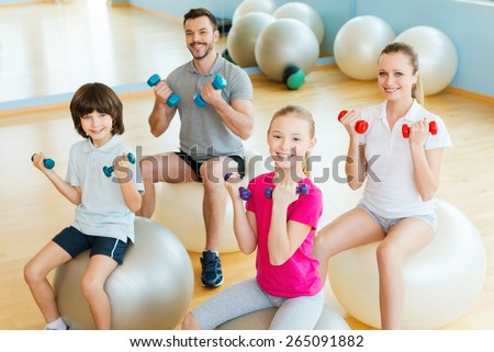 Enjoying time in sorts club. Top view of happy sporty family exercising with dumbbells in sports club while sitting on the fitness balls together - stock photo