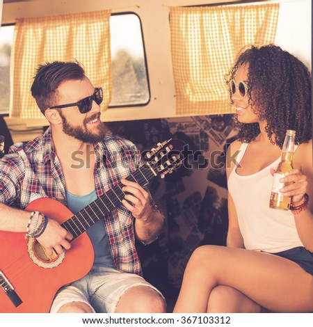 Enjoying time together. Cheerful young beard man sitting in retro minivan and playing guitar while beautiful young African woman looking at him and smiling - stock photo