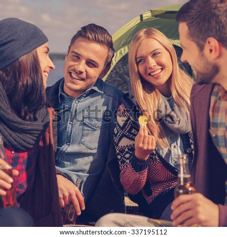 Enjoying time together. Group of young cheerful people drinking beer and talking while camping at the riverbank - stock photo