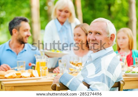 Enjoying time with family. Happy family of five people sitting at the dining table outdoors while senior man looking over shoulder and smiling  - stock photo