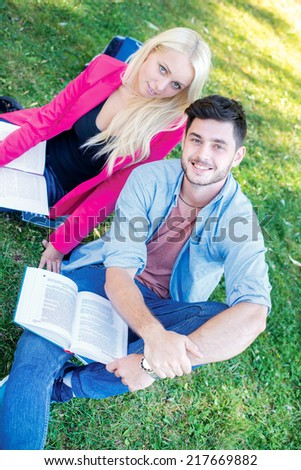 Enjoying university life. Student girl and boy student holding books and looking  at the camera while sitting on the grass near the building of the university on a break. - stock photo