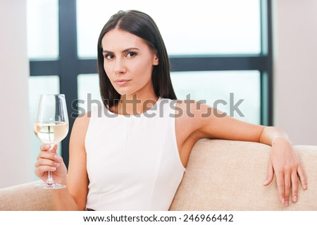 Enjoying white wine. Beautiful young blond hair woman in evening gown sitting on the couch and holding glass with white wine  - stock photo