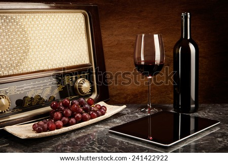 Enjoying wine with old music and modern technology - stock photo