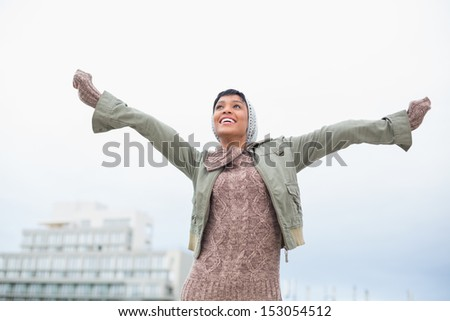 Enjoying young model in winter clothes having fun outside on a cloudy day - stock photo