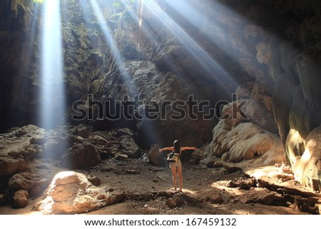 Enjoyment - a happy woman enjoying sunlight pouring into a cave. Beautiful woman in white dress  with arms outspread and face raised see beam light  enjoying peace, serenity in nature  - stock photo