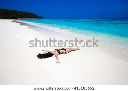 Enjoyment. Beautiful brunette lying On Tropical Beach. Sexy bikini girl model tanned on white sand by sea, exotic island. Summer holidays background. Bliss freedom concept. - stock photo