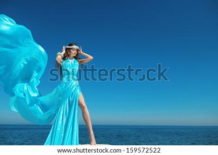 Enjoyment. Fashion model woman with blowing dress over blue sky, outdoors. Brunette girl