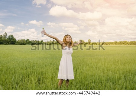 Enjoyment - free happy woman enjoying blue sky and sunrise. Beautiful woman in white dress with holding a water bottle in hand enjoying peace, serenity in green meadow