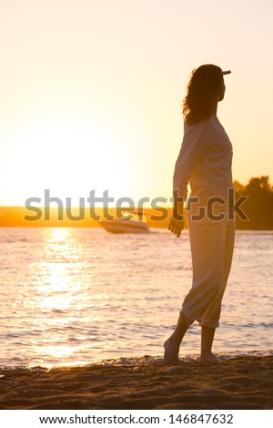 Enjoyment - free happy woman enjoying sunset. Beautiful woman in natural white shirt looking to the golden sunshine glow of sunset with arm near face enjoying peace, serenity in nature - stock photo