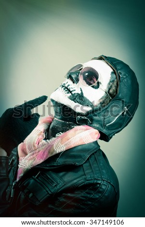 Enlightening aviator with face painted as human skull - stock photo