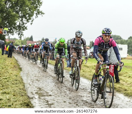 ENNEVELIN, FRANCE - JUL 09:The peloton riding on a cobbled road during the stage 5 of Le Tour de France in Ennevelin on July 09 2014. . - stock photo