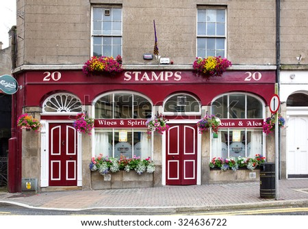 ENNISCORTHY, IRELAND - AUGUST 16, 2015: Stamps public house. It is a quaint Irish pub built in 1844 fronted with a concrete brick cobbled footpath. - stock photo