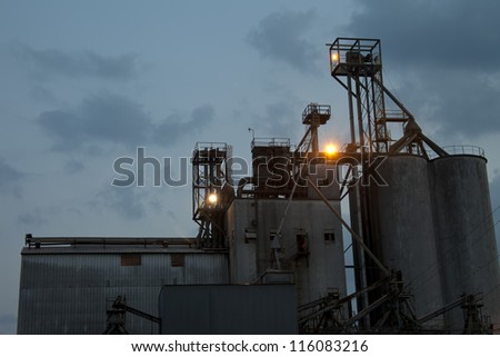 Enormous industrial building backed with a cloudy night sky - stock photo