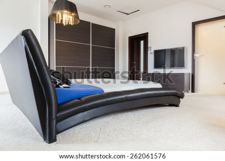 Enormous leather bed in big luxury room - stock photo