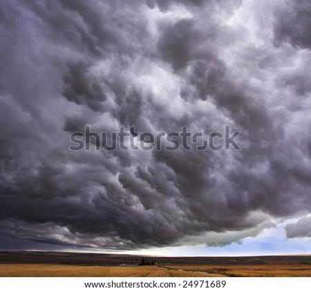 Enormous storm cloud above an autumn field - stock photo