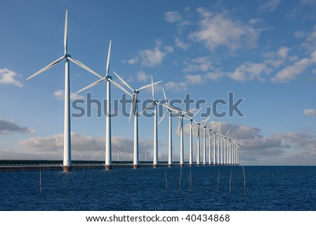 Enormous windmills standing in the sea along a Dutch sea barrier