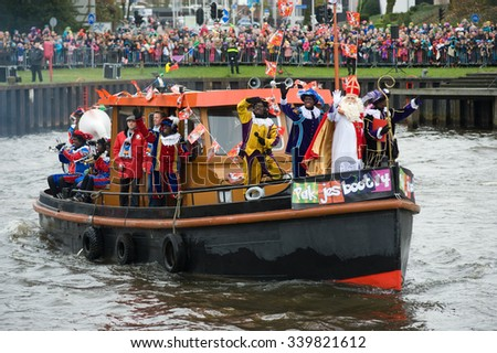 ENSCHEDE, THE NETHERLANDS - NOV 14, 2015: The dutch Santa Claus called 'Sinterklaas' is arriving with his helper Black Pete on a steamboat in a harbor in Holland. - stock photo