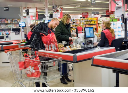 ENSCHEDE, THE NETHERLANDS - OCT 15, 2015: A couple is paying het products they just bought in the Dirk supermarket at the cashier.