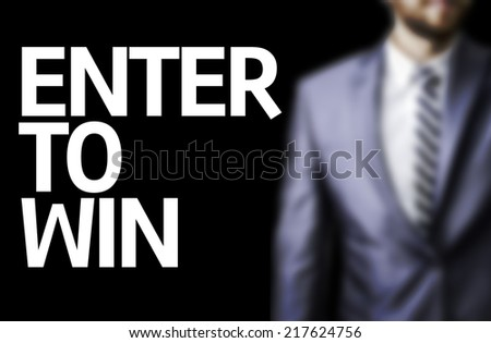 Enter to Win written on a board with a business man on background - stock photo