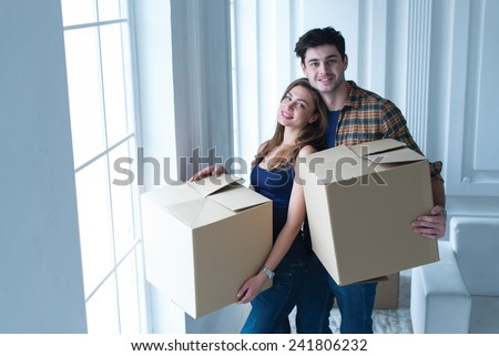 Entering new house. Young and beautiful couple is moving to new apartment surrounded with plenty of cardboard boxes. Both are standing near the window and holding boxes - stock photo