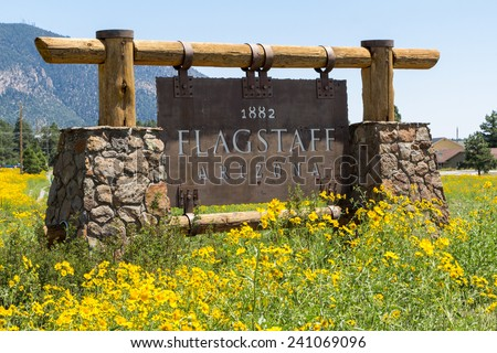 Entering sign Flagstaff in a mountain landscape with yellow flowers - stock photo