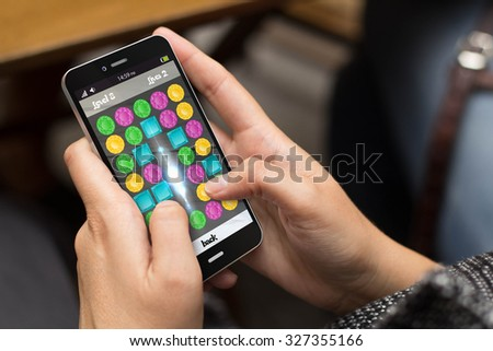 entertainment concept: girl using a digital generated phone with videogame on the screen. All screen graphics are made up. - stock photo
