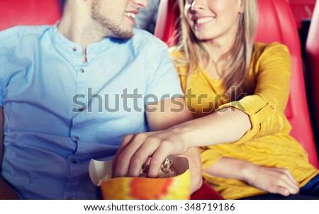 entertainment, leisure and people concept - close up of happy couple watching movie and eating popcorn in theater or cinema - stock photo