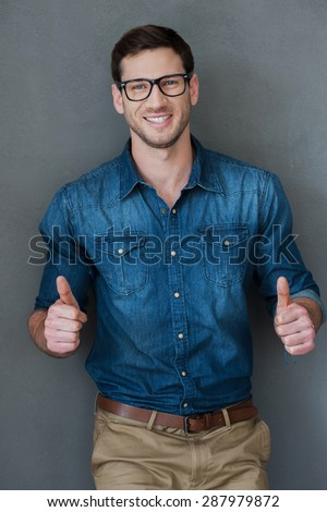 Enthusiastic approval. Cheerful young man holding thumbs up and smiling while standing against grey background - stock photo