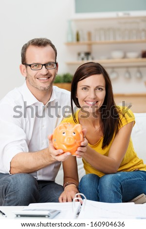 Enthusiastic attractive young couple planning for the future sit side by side on a sofa in the living room holding a piggy bank with an open file and calculator in front of them - stock photo