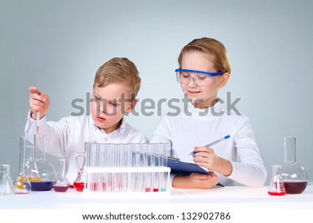 Enthusiastic boy and girl experimenting and writing down the results - stock photo