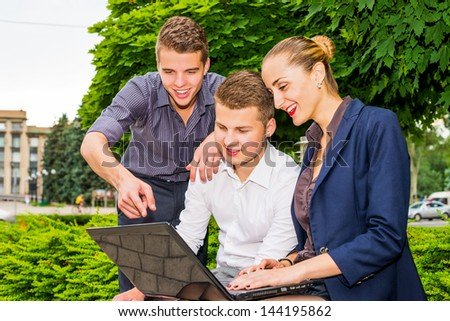 Enthusiastic business people using  laptop outdoors