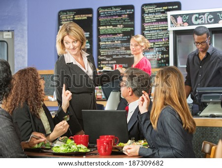 Enthusiastic cafe owner talking with group of customers - stock photo