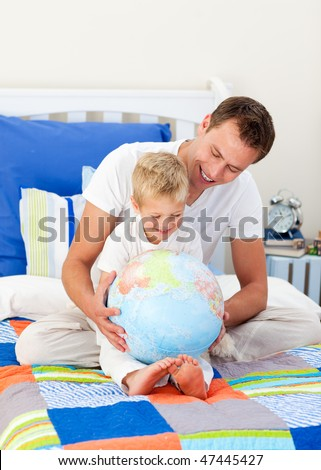 Enthusiastic father and his son looking at a terrestrial globe sitting on bed - stock photo