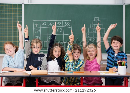 Enthusiastic group of young kids in class sitting in a row at their desk raising their hands in the air to show the know the answer to a question - stock photo
