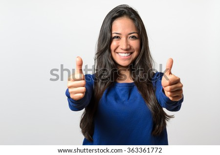 Enthusiastic motivated attractive young woman giving a thumbs up gesture of approval and success with a beaming smile - stock photo