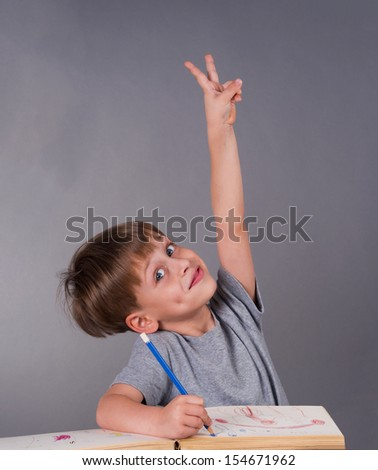 enthusiastic schoolboy raising his hand to give an answer, education concept  - stock photo