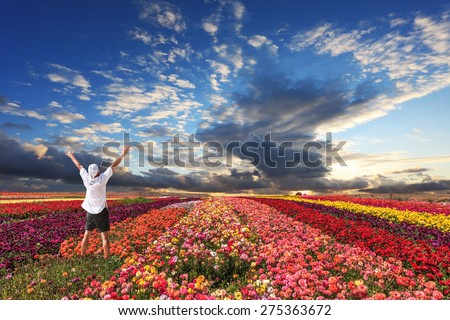 Enthusiastic tourists threw up his hands. Cloudy and windy spring day. Bright festive red, pink and yellow  blooming field of buttercups - stock photo