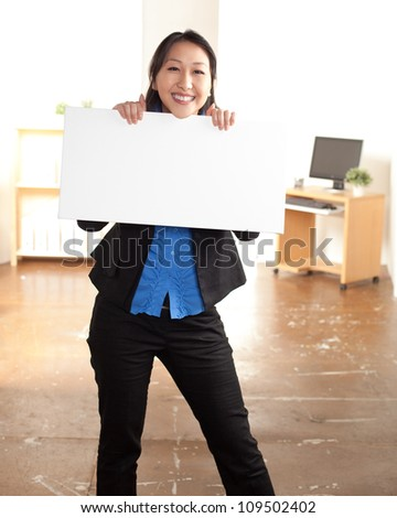 Enthusiastic young Asian woman holding a blank sign wearing a black suit and blue shirt with long straight black hair. - stock photo